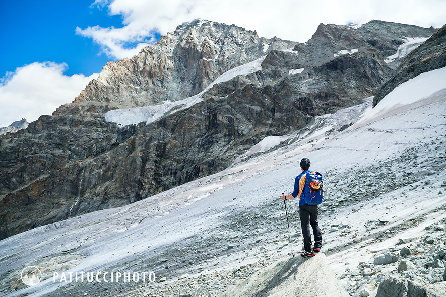 A climber stops to look at the 4357 meter Dent Blanche after climbing it, and now headed down. Switzerland.