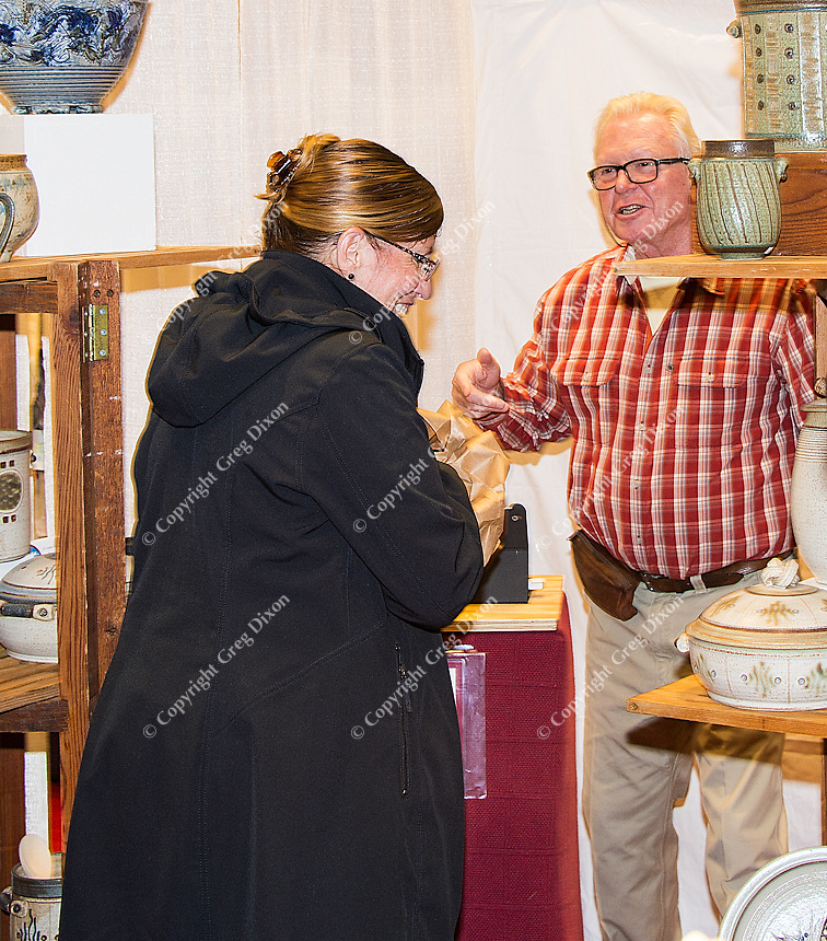 Bart Sheard helps customers purchase Linda Sheard's ceramics and stoneware at The Winter Art Fair Off the Square at Monona Terrace Community and Convention Center on Sunday, November 15, 2015 in Madison, Wisconsin