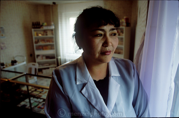 (MODEL RELEASED IMAGE). Oyuntsetseg (Oyuna) Lhakamsuren at her 24-hour pharmacy. On certain nights, when Oyuna has to work late, her son Batbileg will walk a meal over to her and then the two of them will sit down with Oyuna's husband, Regzen Batsuuri, and a niece, to eat their dinner. (Supporting image from the project Hungry Planet: What the World Eats.)