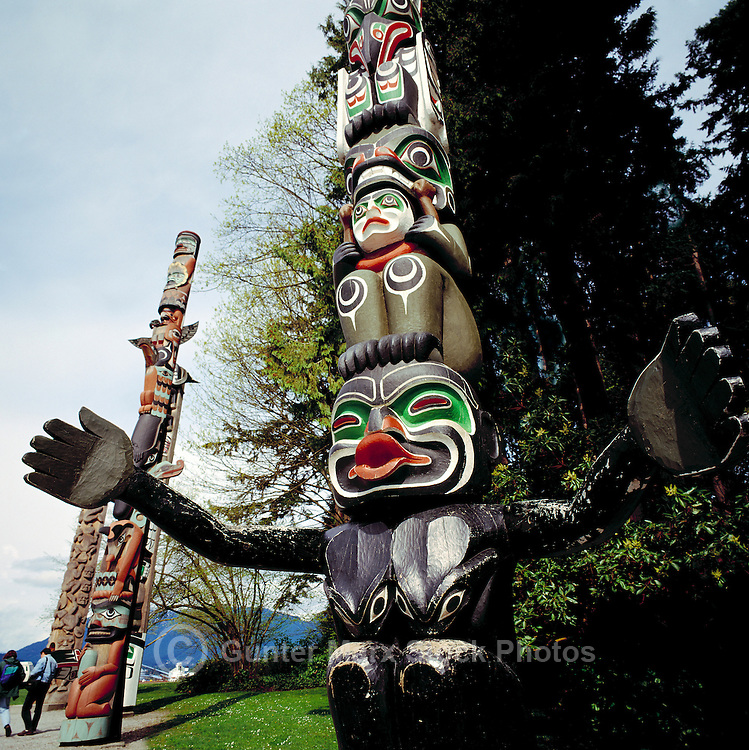 Kwakwaka'wakw (Kwakiutl) Totem Pole, called Ga'akstalas, at Brockton Point in Stanley Park, Vancouver, BC, British Columbia, Canada, in Spring.  Grizzly Bear sits above Dzoonokwa (Wild Woman of the Woods).  Totem Poles in the background are, from left to right: Nisga'a (Nishga) and Nuu-Chah-Nulth.