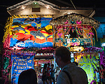 The Buri Bag Project's own Mark Bauer and another judge consider the colorful decorations of a home participating in the Sampaloc Bulihan Festival's decorating contest.  Judging this year was done at night; the winning home won 15,000 Philippine Pesos contributed by the Buri Bag Project.  (Sampaloc, Quezon Province, the Philippines)