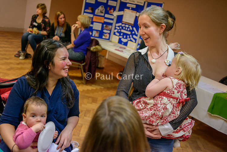 A mother breastfeeding her toddler while talking to other mothers at a conference.<br /> <br /> Image from the breastfeeding collection of the &quot;We Do It In Public&quot; documentary photography picture library project: <br />  www.breastfeedinginpublic.co.uk<br /> <br /> <br /> Middlesex, England, UK<br /> 2016<br /> <br /> &copy; Paul Carter / wdiip.co.uk
