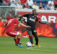 AC Milan midfielder Clarence Seedorf (10) pokes the ball away from oncoming Chicago Fire midfielder Logan Pause (12).  AC Milan defeated the Chicago Fire 1-0 at Toyota Park in Bridgeview, IL on May 30, 2010.