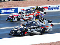 Mar 30, 2014; Las Vegas, NV, USA; NHRA funny car driver Cruz Pedregon (near lane) races alongside Courtney Force during the Summitracing.com Nationals at The Strip at Las Vegas Motor Speedway. Mandatory Credit: Mark J. Rebilas-