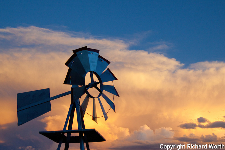 A lawn decoration, a windmill, in a Colorado yard at sunset.  Some things work facing into the wind, not with it at their back.