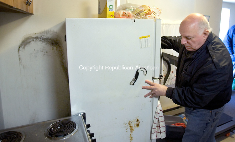 NAUGATUCK, CT. 24 January 2012-012412SV06-Emidio Cerasale of Naugatuck moves a refrigerator from a neighbor's apartment to show the mold growing on the wall behind it at the Oak Terrace apartment complex in Naugatuck Tuesday. People are complaining of mold at the Oak Terrace complex, which is run by the Naugatuck Housing Authority. .Steven Valenti Republican-American
