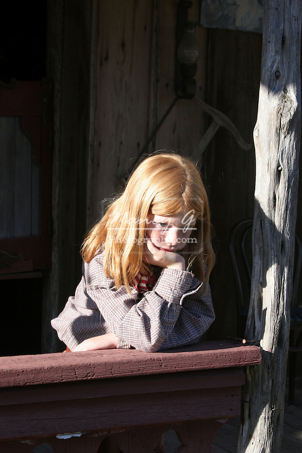 A young cowgirl looking bored in an old west town