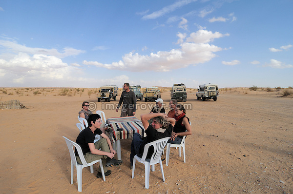 Africa, Tunisia, nr. Ksar Rhilane. A group of 10 desert travellers with their five historic Series Land Rover vehicles having a break from a long days drive at a typical small desert coffee shop close to Ksar Rhilane.  --- No releases available, but releases may not be needed for certain uses. Automotive trademarks are the property of the trademark holder, authorization may be needed for some uses.  --- Info: Image belongs to a series of photographs taken on a journey to southern Tunisia in North Africa in October 2010. The trip was undertaken by 10 people driving 5 historic Series Land Rover vehicles from the 1960's and 1970's. Most of the journey's time was spent in the Sahara desert, especially in the area around Douz, Tembaine, Ksar Ghilane on the eastern edge of the Grand Erg Oriental.