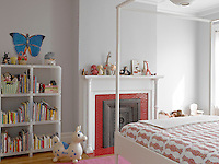 The bright red tiles of this bedroom fireplace creates a bold feature against the pale grey walls