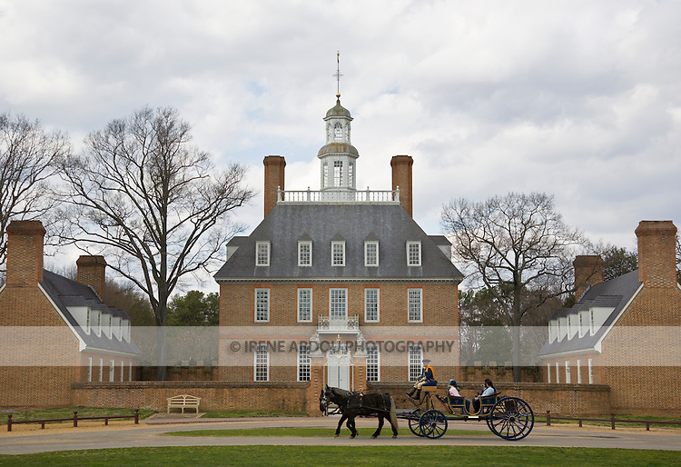 A horse-drawn carriage passes the Governor's Palace in Colonial Williamsburg, Virginia.  Horse-drawn carriage was the principal mode of transport during the time of Colonail Williamsburg.