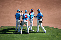 Spokane Indians infielders Jax Biggers (1), Diosbel Arias (21), Cristian Inoa (4), and Curtis Terry (28) wish each other good luck before a Northwest League game against the Vancouver Canadians at Avista Stadium on September 2, 2018 in Spokane, Washington. The Spokane Indians defeated the Vancouver Canadians by a score of 3-1. (Zachary Lucy/Four Seam Images)