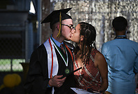 Graduate Blake Slocum kisses Aaliyah Maurice, Friday, July 17, 2020 during a graduation ceremony at Bentonville High School in Bentonville. Check out nwaonline.com/200718Daily/ for today's photo gallery. <br /> (NWA Democrat-Gazette/Charlie Kaijo)