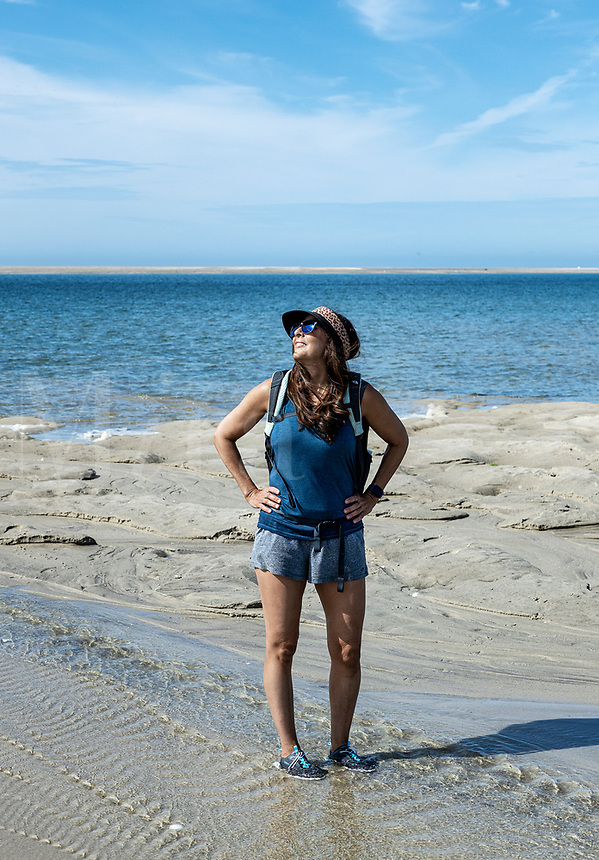 Woman enjoys sunshine and cool ocean water while hiking, Chatham, Cape Cod, Massachusetts, USA.