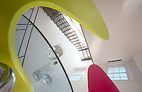 Photographed from a vantage point below the glass dining table the dramatic open staircase of the double-height living area of a London house designed by Richard Rogers