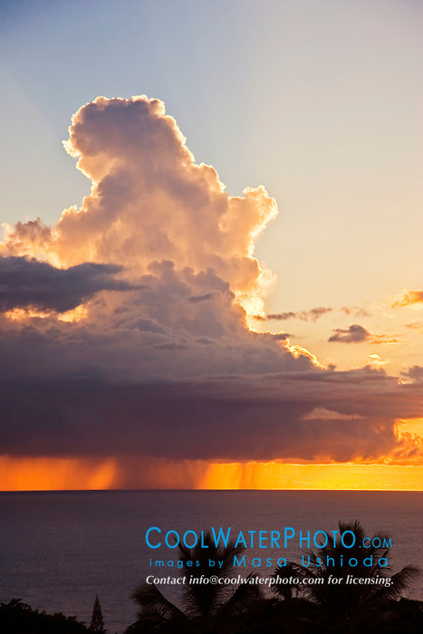 Offshore thunderstorm at sunset with heavy rain pouring from enormous cumulonimbus clouds, Kona Coast, Big Island, Hawaii, Pacific Ocean.