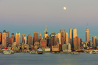 The waxing gibbous moon sits high in the magenta colored twilight sky over the New York City skyline the day before the full moon, as the orange glow of the sunset in the west reflects off the windows and facades of the Manhattan skyscrapers.