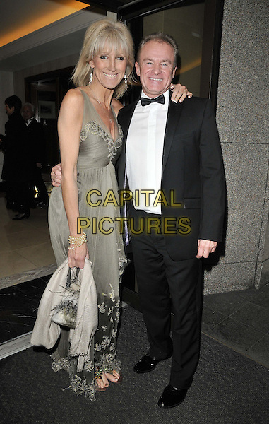 Guest & Bobby Davro..attended the Rhys Daniels Trust Butterfly Ball, Lancaster London hotel, Lancaster Terrace, London, England, UK, .19th November 2011..full length grey gray long maxi dress arm around  black tuxedo bow tie .CAP/CAN.©Can Nguyen/Capital Pictures.