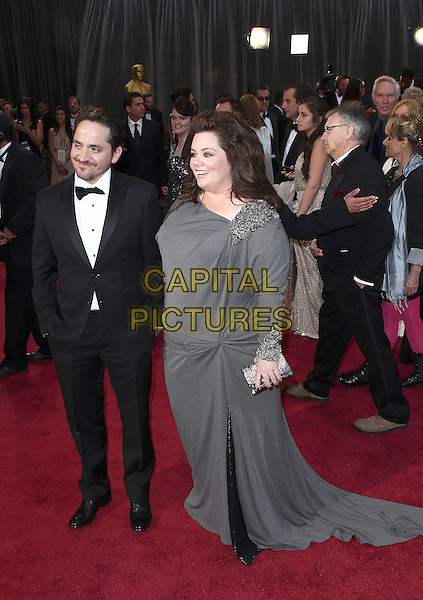 Ben Falcone, Melissa McCarthy.85th Annual Academy Awards held at the Dolby Theatre at Hollywood & Highland Center, Hollywood, California, USA..February 24th, 2013.oscars full length dress grey gray embellished jewel encrusted clutch bag tuxedo black white shirt married husband wife .CAP/ADM/SLP/COL.©Colin/StarlitePics/AdMedia/Capital Pictures