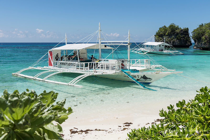 Anda, Bohol, Philippines; wooden, outrigger dive boats, also known as pump boats, are anchored in shallow water in early morning sunlight in front of Amun Ini Resort