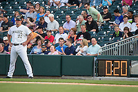 The new 20 second pitch clock can be seen behind Charlotte Knights first base coach Dan Black (27) during the International League game against the Norfolk Tides at BB&T BallPark on April 9, 2015 in Charlotte, North Carolina.  The pitch clock is one of several pace of game rules being tested at the Double-A and Triple-A levels of Minor League Baseball during the 2015 season.   (Brian Westerholt/Four Seam Images)