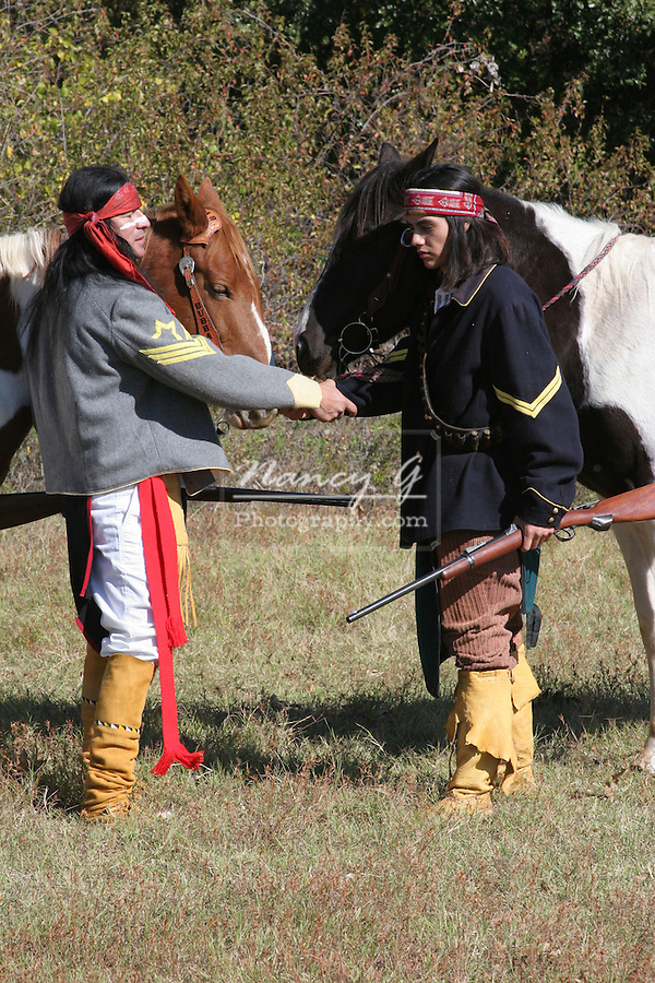 Two Apache Native American Indians with their horses greeting eachother