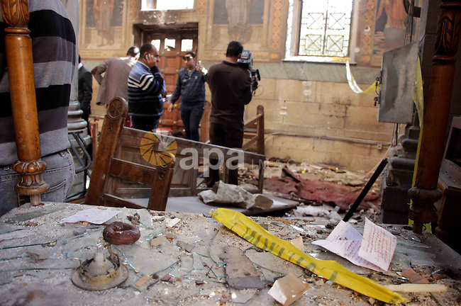 Egyptian security officials and investigators inspect the scene following a bombing inside the Saint Peter and Saint Paul Coptic Orthodox Church in Cairo's Abbasiya neighbourhood on December 11, 2016, . The blast killed at least 25 worshippers during Sunday mass inside the Cairo church near the seat of the Coptic pope who heads Egypt's Christian minority, state media said. Photo by Amr Sayed