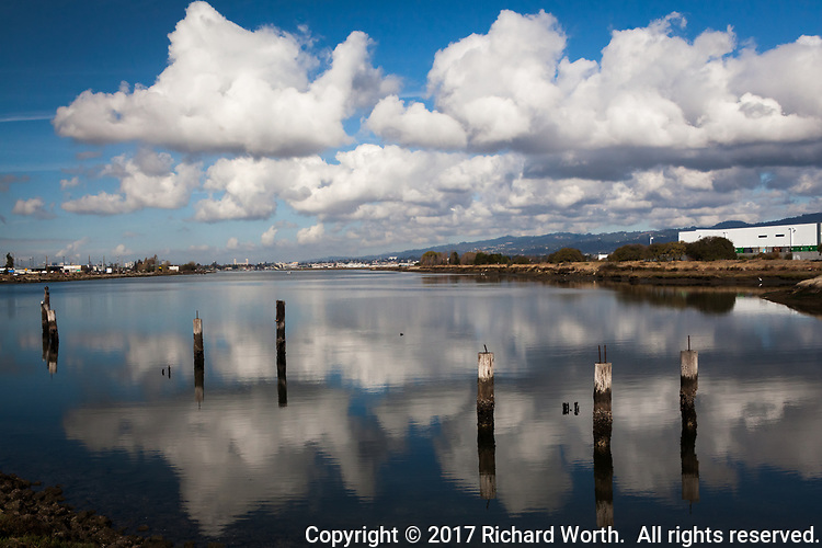 Clouds float in the sky while their reflections float in the water of San Leandro Bay at the Martin Luther King Jr. Regional Shoreline next to the Oakland International Airport.