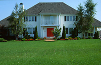 Beautiful lawn with lovely Colonial style suburban house, blue sky