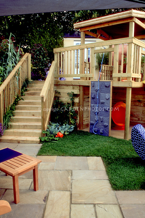 Child's climbing area onto deck with lawn, stone patio, stairs to raised deck, house, with kids in mind