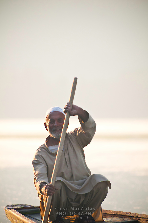 Smiling man paddling a traditional Kashmiri shikara, or gondola, at sunrise, Dal Lake, Srinagar, Kashmir, India..
