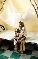 Sudan. West Darfur. Habilah. The non-governmental organization (ngo) Médecins sans Frontières (MSF) Switzerland runs a clinic. A young girl holds in her arms her yougest sister who is severely malnourished. A medical tube is taped on the child's forehead and goes through the nose to facilitate the injection of food. They both seat on a bed near a mosquito net. © 2004 Didier Ruef