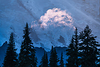 A lone cloud is lit up by the setting sun at Mount Rainier Washington.