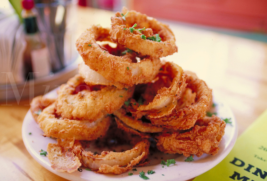 Onion Rings plated and on a restaurant table. Restuarant interior.