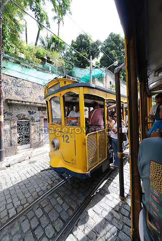 Bonde, Rio's famous electric tram; Rio de Janeiro, Espirito Santo, Brazil. The historic street railway has been transporting Rio residents for over a century. The little yellow tram rattles along the track like an antique roller coaster. Starting from downtown Carioca Station across the Arcos da Lapa (a former aqueduct) it is riding through the neighborhood of Santa Teresa. Seating is on wooden benches, but the local daredevils prefer swinging from the tram's outer poles. --- No releases available.