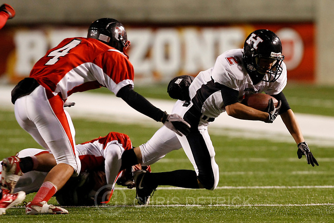 Chris Detrick  |  The Salt Lake Tribune .Hurricane's Nathan Barker #2 is tackled by Delta's Jace Abbott #4 and Colin Christensen #12 during the first half of the 3A Semi-final game at Rice-Eccles Stadium Thursday November 11, 2010.