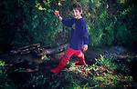 AREMM9 Young boy wearing red wellington boots palying in muddy stream