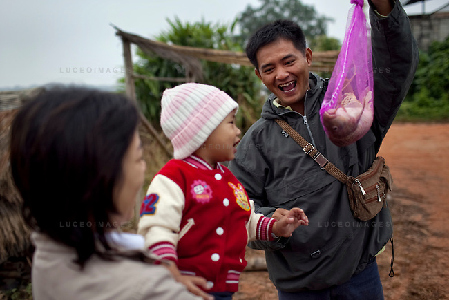 Pornlert Prompanya, 32, right, plays with his son Asia, 2, and wife Ary along the Mekong River in Sop Ruak, Thailand. Pornlert bought the fish from the fishing village for 100 Baht, roughly $3 USD. Photo taken on Thursday, December 10, 2009. Kevin German / Luceo Images
