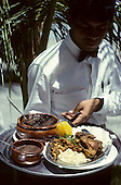 Sao Paulo, Brazil. Feijoada - black beans, rice, manioc flour and meat - served by a waiter wearing a bow-tie.