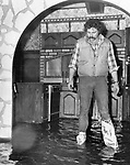 Olin Graham inspects water damage at Custom Craft Kitchens on Division Street after flooding in 1980.
