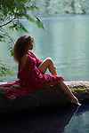 Tranquil romantic portrait on a beautiful young woman sitting on a tree trunk in summer nature scenery with thoughtful expression dipping her foot in calm blue water of a lake