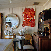 A red painting by Ismail Acar has been tacked to the wall of Carl's studio next to a Renaissance cabinet awaiting restoration