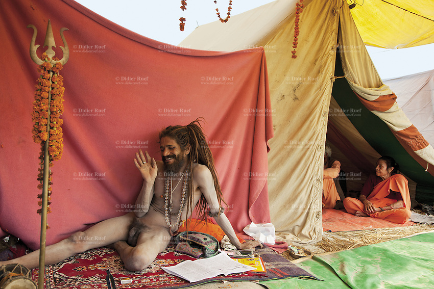 "India. Uttar Pradesh state. Allahabad. Maha Kumbh Mela. A Naga (naked) Sadhu sits on a carpet outside his tent at Sangam. A couple attends spiritual discourses inside the tent. Naga sadhdus were once warriors, that's why they still carry weapons, such as Trishula. A trishula is a type of Indian trident, commonly used as a Hindu religious symbol. The word means ""three spear"" in Sanskrit. In India, the term often refers to a short-handled weapon which may be mounted on a danda or staff. The trishula is wielded by the Hindu God Shiva. The Kumbh Mela, believed to be the largest religious gathering is held every 12 years on the banks of the 'Sangam'- the confluence of the holy rivers Ganga, Yamuna and the mythical Saraswati. In Hinduism, Sadhu (good; good man, holy man) denotes an ascetic, wandering monk. Sadhus are sanyasi, or renunciates, who have left behind all material attachments. They are renouncers who have chosen to live a life apart from or on the edges of society in order to focus on their own spiritual practice. The significance of nakedness is that they will not have any worldly ties to material belongings, even something as simple as clothes. A Sadhu is usually referred to as Baba by common people. The Maha (great) Kumbh Mela, which comes after 12 Purna Kumbh Mela, or 144 years, is always held at Allahabad. Uttar Pradesh (abbreviated U.P.) is a state located in northern India. 6.02.13 © 2013 Didier Ruef"