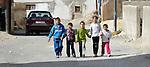 Syrian refugee children walk along a street in Amman, Jordan.