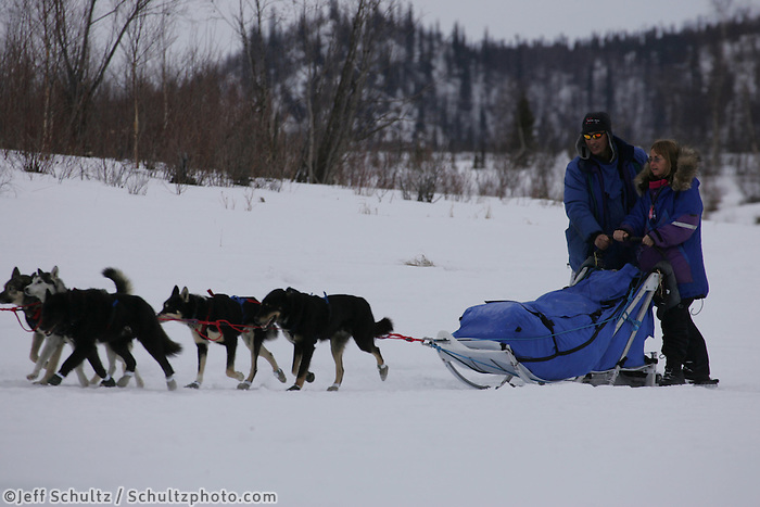 John Baker gives Martin Buser's wife Kathy Choapaton a short ride as he arrives at the half-way Iditarod checkpoint.  2005 Iditarod Trail Sled Dog Race.