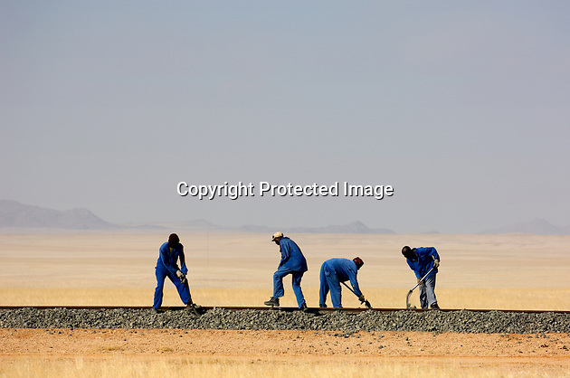 A labour gang working on the dead straight railway track that traverses the Koichab Pan in central Namibia. The work on the track will allow zinc from the Scorpion mine near Rosh Pinah to be transported from Aus to Luderitz for export.