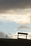 A silhouette of a park bench against a background of building clouds at Zabriski Point, Death Valley National Park.