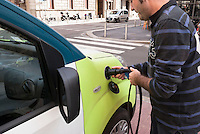 "Milano, car sharing e-vai. Un addetto mette in carica un veicolo elettrico --- Milan, ""e vai"" car sharing. An employee putting an electric vehicle to charge"