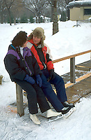 Spouses age 33 and 39 resting after ice skating session at Bracket Park. Minneapolis Minnesota USA