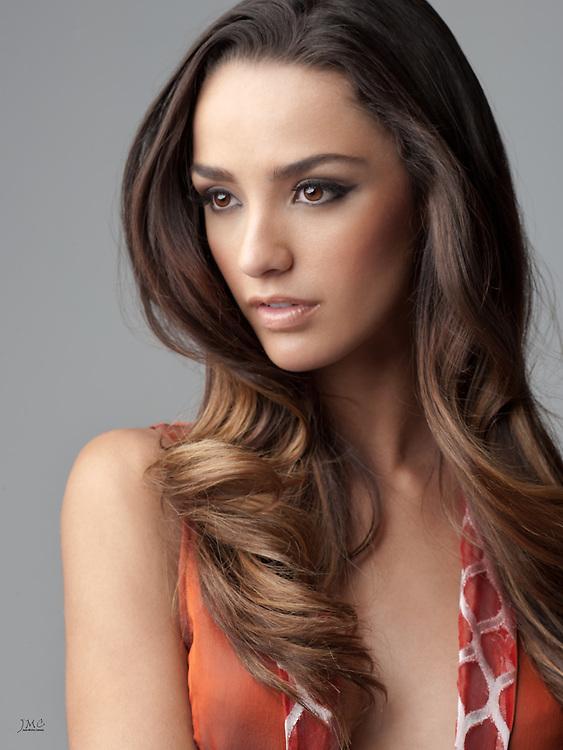 Beautiful brunette fashion model closeup in orange blouse