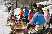 Volunteers assist Dee Dee Jonrowes team in leaving Takotna Chkpt 2006 Iditarod Interior Alaska Winter